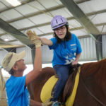 Participant rides horse during therapy session.