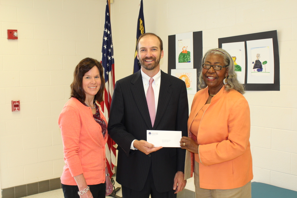Southwest Elementary Principal Dr Brian Muller receives a Principals' Fund for Student Needs grant from Board Member Doris Davis.